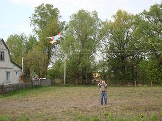 Дед Саша запускает воздушный змей на огороде соседа