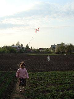 Криситна гуляет по огороду пока папа играет с возушным змеем