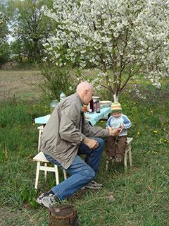 Дед Саша общается с внуком Лукошей и пытается скормить ему зеленый лук